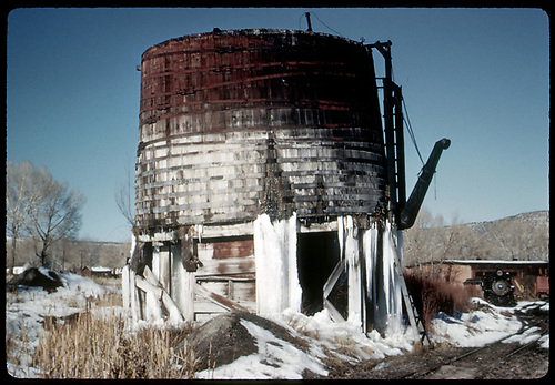 RGS water tank encrusted with ice at Ridgway with #74 and roundhouse in background to right.<br /> RGS  Ridgway, CO  Taken by Kindig, Richard H. - 11/21/1951