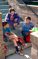 Boy Scouts age 12 waiting for camp sitting on steps talking.  St Paul  Minnesota USA