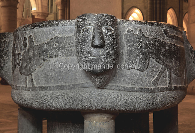Baptismal font, 11th century, in black Tournai stone, with 4 faces representing either the Evangelists, or the 4 Rivers of Paradise (Tigris, Euphrates, Gihon and Pison), on the left a bird with snake tail representing the struggle between good and evil, and on the right an animal figure, in the South transept, Laon Cathedral or the Cathedrale Notre-Dame de Laon, built 12th and 13th centuries in Gothic style, in Laon, Aisne, Picardy, France. The cathedral is listed as a historic monument. Picture by Manuel Cohen.