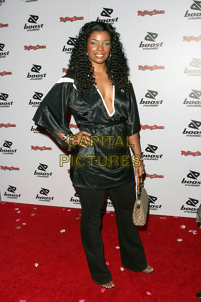 SYLEENA JOHNSON.Kanye West  Post Grammy Party hosted by Boost Mobile and Dave Meyers. Los Angeles, California..February 13th, 2005.Photo Credit: Zach Lipp/AdMedia.full length hand on hip black silk satin top white trim plunging neckline cleavage.www.capitalpictures.com.sales@capitalpictures.com.© Capital Pictures.