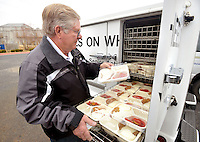 STAFF PHOTO BEN GOFF  @NWABenGoff -- 12/16/14 Mel Deason, driver for Meals on Wheels of Benton County, loads hot meals in the heated compartment of his truck at the Benton County Senior Activity and Wellness Center in Bentonville before beginning his rout on Tuesday Dec. 16, 2014. Meals on Wheels of Benton County supplies five extra frozen meals to seniors during the winter in case weather prevents drivers from making their rounds and will be distributing special holiday care bags donated by Walmart.