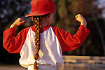 Young girl (7 years old), Little League Baseball player, showing muscles after baseball game, sunset light, portrait, Woodinville, Washington USA  MR