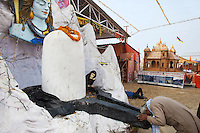 "India. Uttar Pradesh state. Allahabad. Maha Kumbh Mela. Inside the courtyard of a guru's ward, an Indian Hindu devotee bends and prays in front of a sculpture of Shiva and a monkey. Shiva (meaning ""auspicious one"") is a Hindu deity and is considered one of the Supreme God. A model of the Rama temple which will be built in Ayodha at a disputed site between hindus and muslims. A man is sleeping on the ground on straw. The Kumbh Mela, believed to be the largest religious gathering is held every 12 years on the banks of the 'Sangam'- the confluence of the holy rivers Ganga, Yamuna and the mythical Saraswati. The Maha (great) Kumbh Mela, which comes after 12 Purna Kumbh Mela, or 144 years, is always held at Allahabad. Uttar Pradesh (abbreviated U.P.) is a state located in northern India. 12.02.13 © 2013 Didier Ruef"