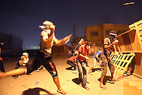 Photographer: Rick Findler..21.04.13 Protesters throw stones at riot police on the front lines of a clash between police and protesters in Ma'ameer, Bahrain. The number of protests in Bahrain increase dramatically during the sporting event to help bring attention to the ruling bahraini Sunni royal family's many human rights abuses and repression of the country's Shiite people.