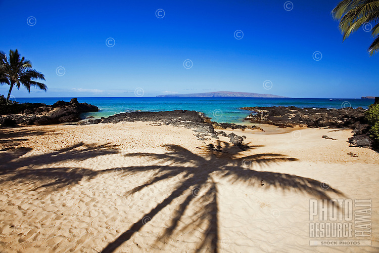 A palm shadow decorates the beach at Makena, Maui.
