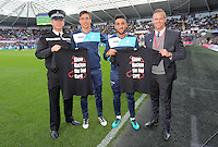 Jack Cork and Neil Taylor with Lee Trundle and a police officer holding Show Racism the Red card t-shirts before the Premier League match between Swansea City and Watford at The Liberty Stadium on October 22, 2016 in Swansea, Wales, UK.