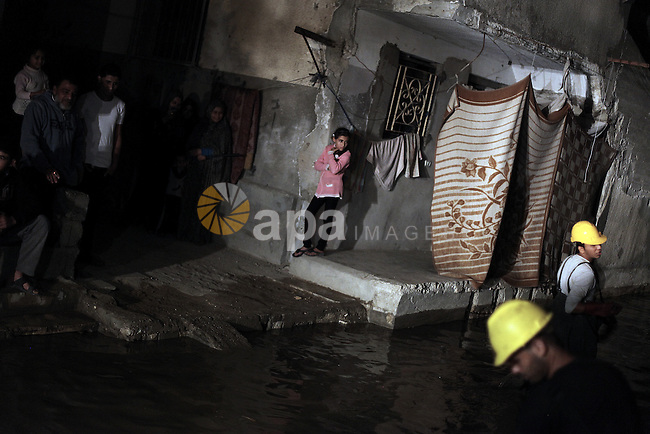 Palestinian workers work in a flooded street with sewage in al-Sabra neighborhood, in Gaza City on November 13, 2013. The main pump of sewage water which serves thousands of citizens in a densely populated area was stoped during the power cuts in the area due to a fuel shortage, causing sewage overflow out of the station in the lower nearby areas. Photo by Ali Jadallah