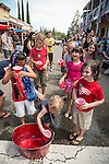 Kids relay water in a race between two teams before the parade. Downtown main street during the Independence Day celebration Main Street, Mokelumne Hill, California