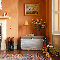 Terracotta painted walls and bare floorboards create a perfect blank canvas for the owners' eclectic mix of furniture in this living room