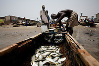 a man sells his catch while awaiting for the 50th anniversary of his countries' independence in the Jamestown neighborhood in Accra, Ghana on Monday March 05 2007..