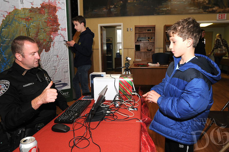 NWA Democrat-Gazette/FLIP PUTTHOFF <br /> CAVE SPRINGS CHRISTMAS<br /> Patrolman Scott Hammersla (cq) helps Juan Quezada, 8, (cq) record his thumb print Saturday DEc. 10 2016 during the Christmas in Cave Springs event held downtown. The city and the Illinois River Watershed Partnership sponsored the holiday festivities that included also included visits with Santa, holiday craft making, nature hikes and Christmas caroling.
