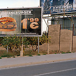 Hollywood-style billboards and fast food adverts are planted on the edge of a lemon-grove on the periphery of Alicante.