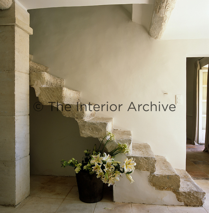 A bucket of freshly cut flowers next to the rustic stone staircase of the entrance hall