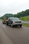 Chevy HD truck towing trailer with skid steer