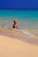 Child playing in the water at Lanikai beach, Oahu