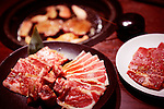 Plates with raw meat at Japanese grill restaurant. Yakiniku, Japanese barbecue.