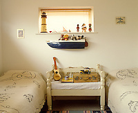 In a restored beach house in Camber Sands fun junk shop treasures adorn a wall and window sill of a child's bedroom