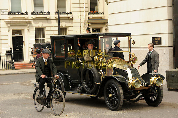Calum Callaghan.Filming of 'Mr Selfridge' in London, England..6th May 2013.film on the set of acing actors cast crew full length costume black coat suit car.CAP/IA.©Ian Allis/Capital Pictures.