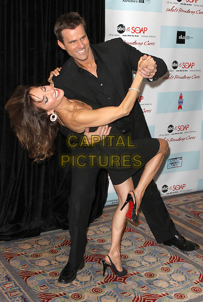 SUSAN LUCCI & CAMERON MATHISON.5th Annual ABC & SOAPnet salute Broadway Cares/Equity Fights AIDS Benefit held at Marriott Marquis New York City, New York, NY, USA..March 9th, 2009.full length black dress shirt trousers holding hands dancing dip bending leaning gesture strapless .CAP/ADM/PZ.©Paul Zimmerman/AdMedia/Capital Pictures.