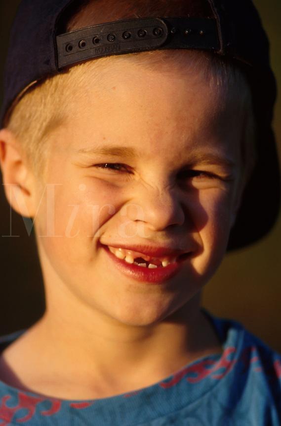 Happy boy woth missing teeth and baseball cap.