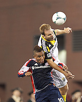 New England Revolution midfielder Juan Agudelo (10) and Columbus Crew defender Chad Marshall (14) battle for head ball.  In a Major League Soccer (MLS) match, the New England Revolution (blue) defeated Columbus Crew (white), 3-2, at Gillette Stadium on October 19, 2013.