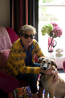Nicky Tibbles and her dog sitting in the light of the half-landing at her Notting Hill home