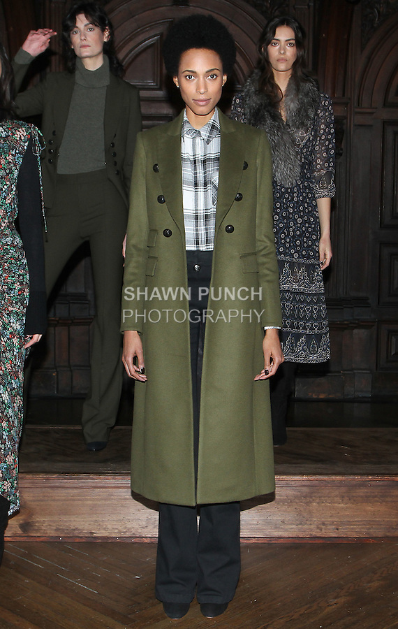 """Model Kelley poses in a black/white crinkle plaid button down, army green wool cashmere faux double breasted dickey coat, and black stretch denim sailor skinny flare, from the Veronica Beard Fall 2016 """"Gypsy Caravan"""" collection presentation, at the Highline Hotel on February 15 2016, during New York Fashion Week Fall 2016."""