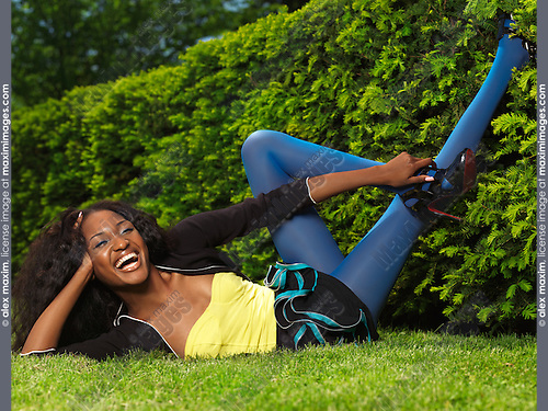 Laughing young stylish woman in colorful clothes lying on green grass