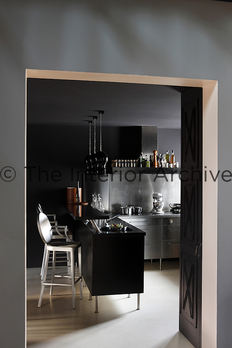"The dramatic black kitchen is furnished with stools by Philippe Starck and black glass ""Artemide"" pendant lights"