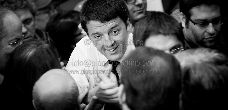 Matteo Renzi shakes hands to some supporters as he joins a political campaign convention of Partito Democratico - the Italian left-wing Party- for the Italian government elections in Turin, April 12, 2014.