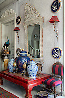 In the entrance of the reception room, a collection of porcelain ginger jars and other objects are arranged on an antique Chinese red table and Arabic calligraphy ceramic plates hang on the wall. The layers of colours, patterns and textures add to the opulent feel of the room.