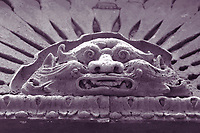Taranto: In the historical center,  the suggestive particular of the old decoration on the top of a front door. It is a bas relief that depicts a quite monstrous and tired face, that is surrounded by rays, and that therefore suggests the sun. Monochrome. This is a slight enlargement of a part of the original photo.<br /> <br /> You can download this file for (E&amp;PU) only, but you can find in the collection the same one available instead for (Adv).