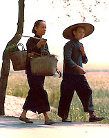 Two women walking along country lane.Pictures taken in Canton China in 1977 at the time of the cultural revolution.