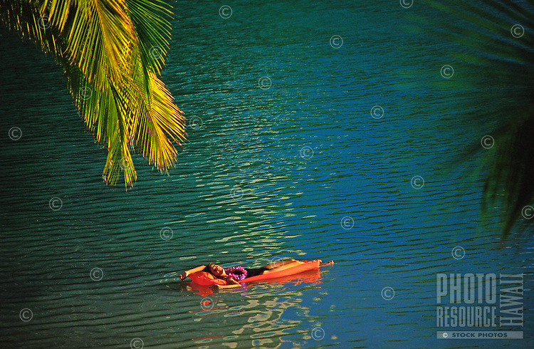 Woman floating on an orange air mattress in the Hilton lagoon, surrounded by palm frons, Waikiki