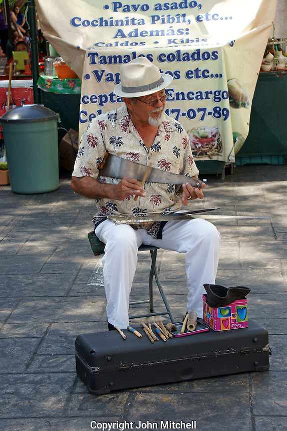 Street musician playing a carpenter's saw in Merida, Yucatan, Mexico