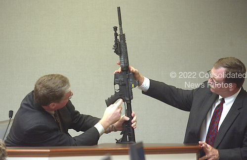 Timothy Curtis, supervisor of the firearms section of the Bureau of Alcohol, Tobacco, and Firearms (ATF), left, points out features on a Bushmaster rifle used in the sniper shootings as it is held by Prince William County (Virginia) prosecutor Richard Conway, right, during testimony in the trial of sniper suspect in courtroom 10 at the Virginia Beach Circuit Court in Virginia Beach, Virginia on November 3, 2003.<br /> Credit: Lawrence Jackson - Pool via CNP