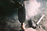 With mallets and the anvil, the blacksmiths can make hoes, sickles, axes. A hole is made in the wooden handle to connect the iron implements.