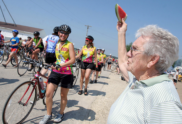 Marjorie Buck of Grundy Center hawks watermelon slices to riders arriving in Kesley.