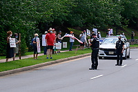 A police officer appears to document protester activity with  a cell phone outside the Trump National Golf Club in Sterling, Virginia, U.S., on Saturday, August 1, 2020.<br /> Credit: Erin Scott / Pool via CNP /MediaPunch