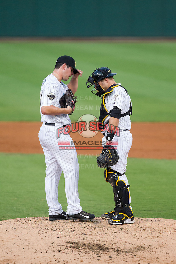 Charlotte Knights catcher Josh Phegley (4) has a chat on the mound with starting pitcher Carlos Rodon (41) during the game against the Gwinnett Braves at BB&T Ballpark on August 19, 2014 in Charlotte, North Carolina.  The Braves defeated the Knights 10-5.   (Brian Westerholt/Four Seam Images)