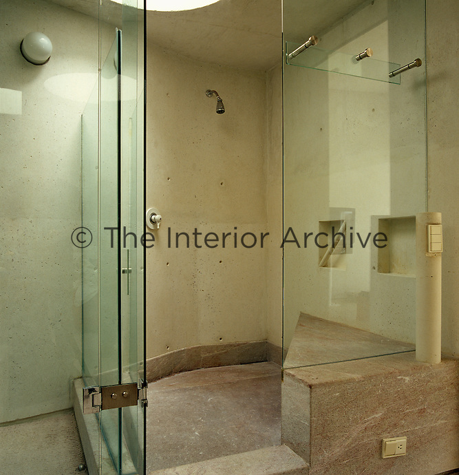 This large walk-in shower has a marble floor and walls of concrete