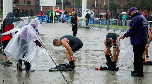 10 AUG 2014 - LIVERPOOL, GBR - Competitors pull their wetsuits off after finishing the swim leg of their race at the Tri Liverpool triathlon which incorporated the 2014 British Age Group Triathlon Championships in Kings Dock in Liverpool, Great Britain (PHOTO COPYRIGHT © 2014 NIGEL FARROW, ALL RIGHTS RESERVED)
