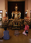 Visitors pay homage to the golden image of Buddha in Bangkok, Thailand. The great Buddha, a solid five and a half ton gold, statue cast 700 years ago, vanished from its dias during an invasion by the Burmese. In 1955, a heavy but nondescript state of Buddha was found in Northern Thailand, When a heavy crane was used to lift it, the crane and hoist broke and the statue fell,. When the outer flesh of cement cracked and the gold glittered, a lost treasure was found. (Jim Bryant Photo)........