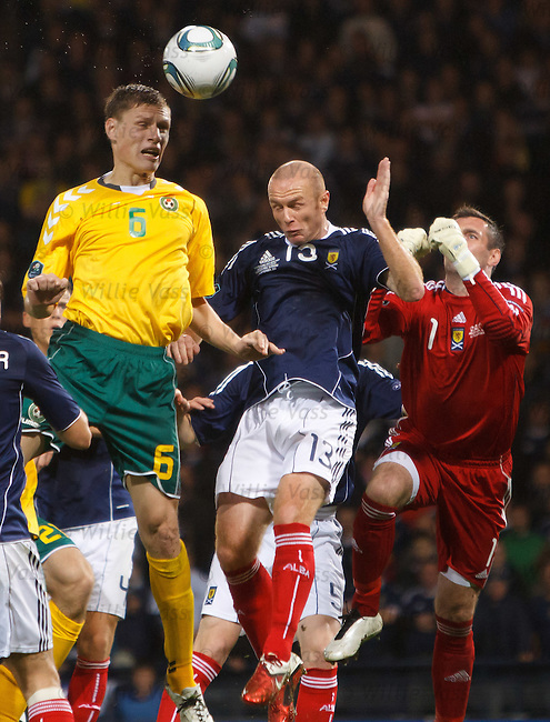 Marius Zaliukas challenged in the box by Stephen Crainey and Allan McGregor
