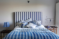 A guest bedroom decorated in a palette of blue and white with floral and striped linens are combined to great effect. The cool colour scheme creates a calm mood.