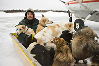 First year veterinarian, David Palmini, sits in a sled behind a snowmachine to help bring dropped dogs to the airport at Nikolai during 2008 Iditarod
