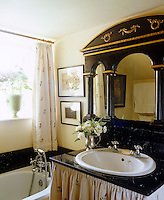 A black Empire-style mirror and washstand matched with pink floral curtains is an unusual but effective combination in the tiny bathroom