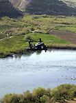 A UH-60 Blackhawk helicopter flies over the Tigris River, transporting Soldiers to a Forward Operating Base near Mosul. When transporting Soldiers, the gunners and pilots are also looking for enemy activity.