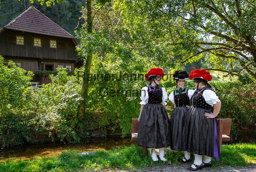 Germany, Baden-Wurttemberg, Kirnbach (Wolfach): three young women in famous Black Forest costume with red and black Bollenhat | Deutschland, Baden-Wuerttemberg, Ortenaukreis, Kirnbach (Wolfach): drei junge Frauen auf dem Kirnbacher Bollenhut-Talwegle in der beruehmten Kirnbacher Tracht mit dem roten und schwarzen Bollenhut, die heute in der ganzen Welt als Schwarzwaelder Tracht bekannt ist