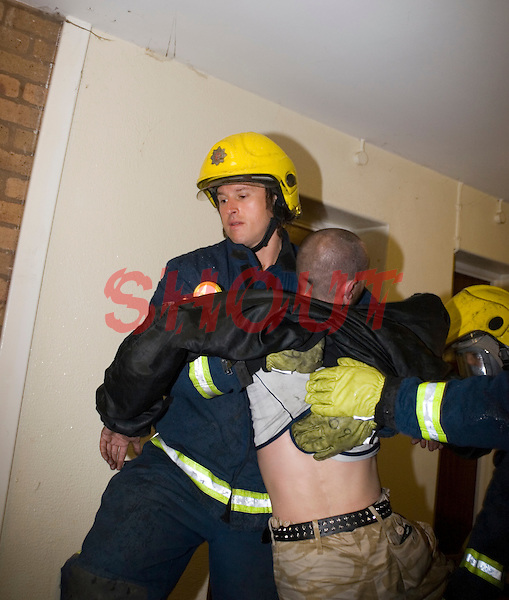 Firefighters wearing BA rescue Male Adult from his burning flat. This image may only be used to portray the subject in a positive manner..©shoutpictures.com..john@shoutpictures.com